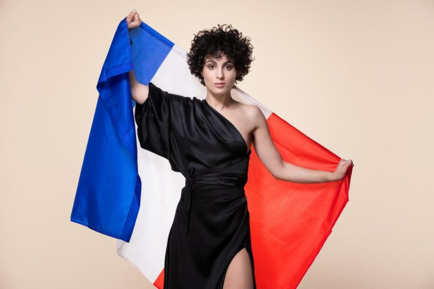 Barbara Pravi in a black dress. She is holding the Franch flag behind her.