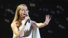 Ana Soklič performs in a white gown. She is holding out her left arm in front of her.